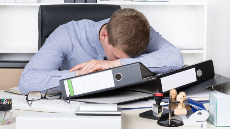 Young Exhausted Man Is Lying On The Desk In Office 770x433